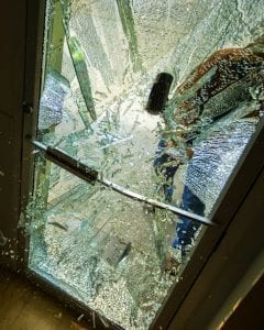 A robber using a sledgehammer to break the glass of a retail store.