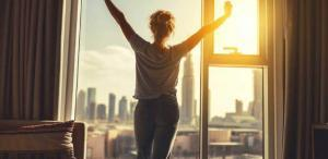 happy-woman-stretches-and--opens-curtains-at-window-in-morning-resized