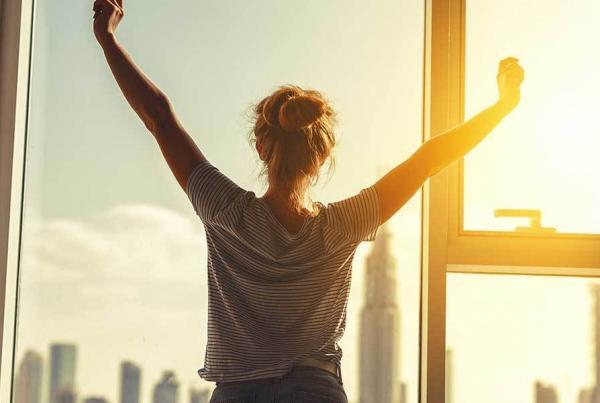 happy-woman-stretches-at-window-in-morning-1600x600