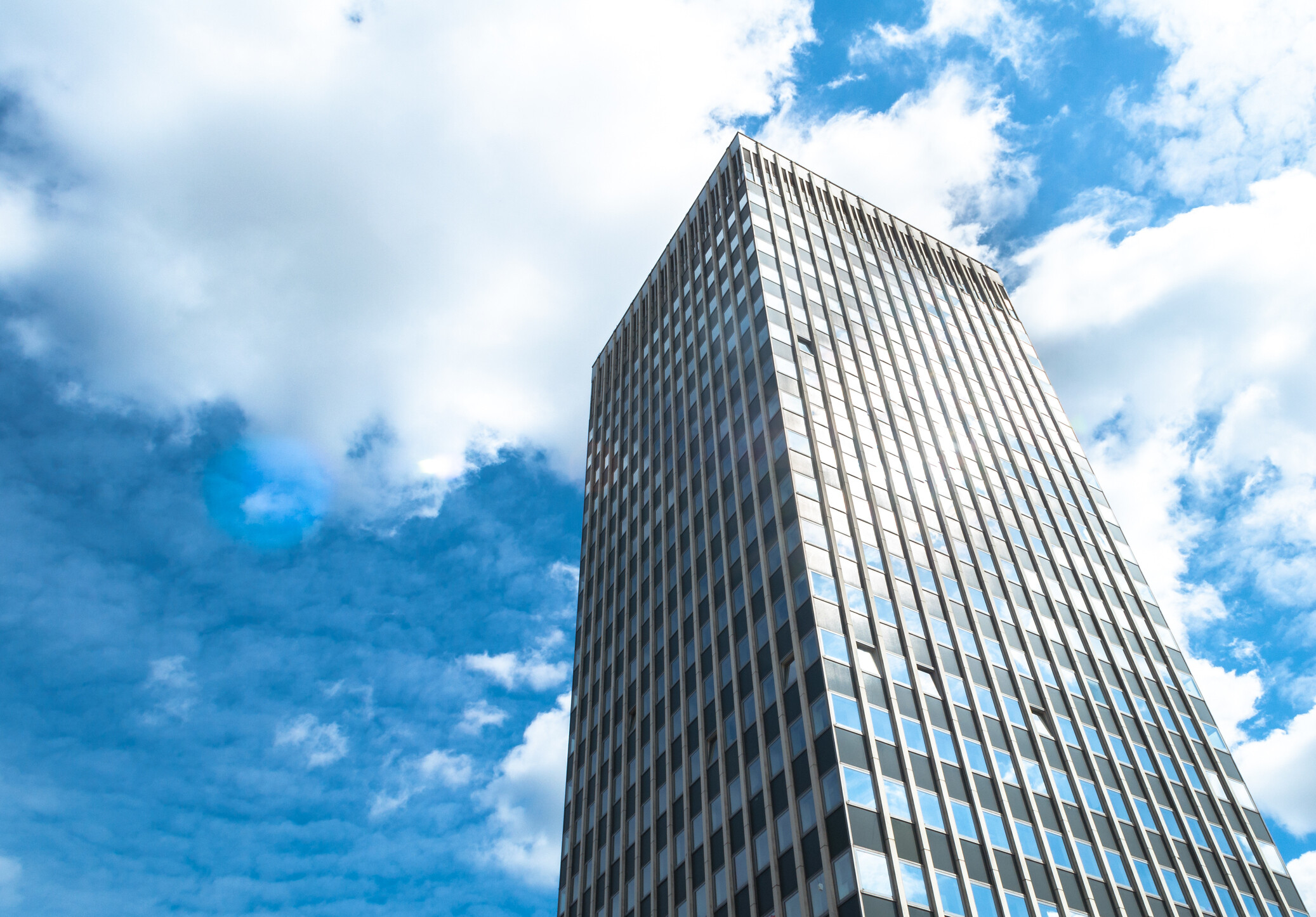 Towering SIngle Office Block with Blue Sky and White Fluffy Clouds